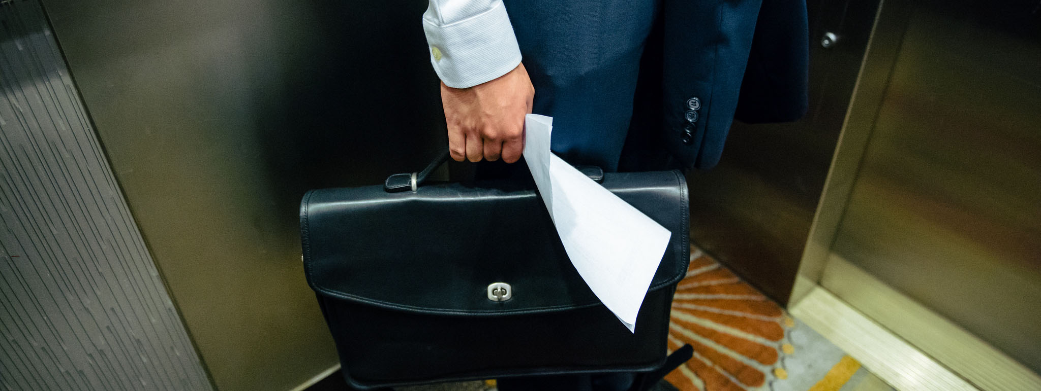 Law student holding a briefcase on an elevator.